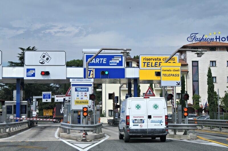 """O pedágio da esquerda é o que recebe dinheiro e cartão, o do centro (que tem a van passando), recebe só cartão, e o do lado direito é o Telepass (""""sem parar"""" italiano)"""